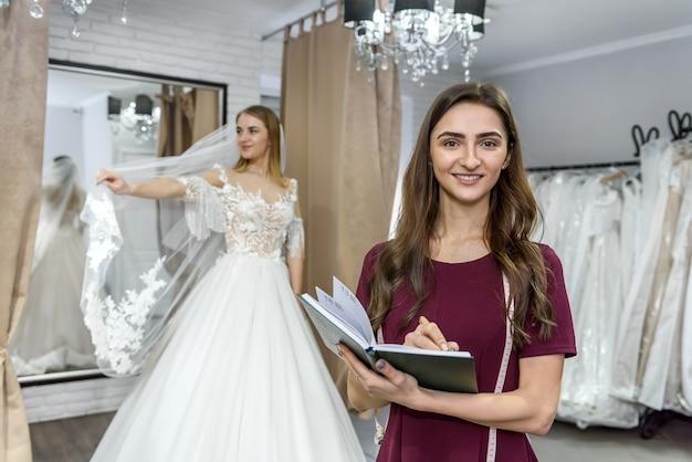 Designer com bloco de notas e noiva com vestido de noiva atrás