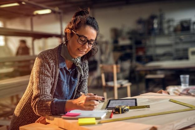 Designer criativa de meia-idade em seu estúdio fazendo através de planos de papel. trabalho tarde da noite.