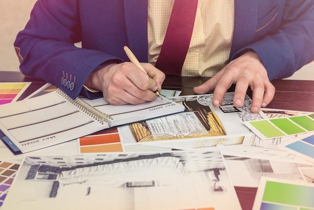 Designer de casa trabalhar no esboço de casa de escritório com catálogo de cores para o apartamento de renovação moderna dos sonhos. planta da casa de arquitetura e amostra de cor