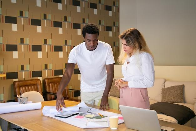 Designer de conteúdo afro-americano explicando o projeto ao cliente e mostrando o rascunho