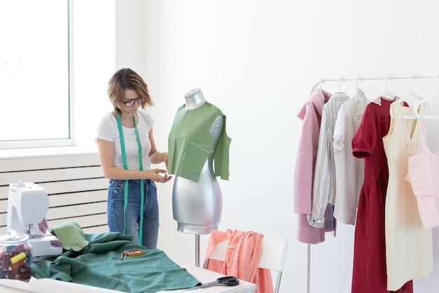 Designer de costureira jovem bonita com óculos e uma fita métrica faz um novo produto