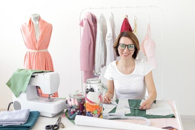 Designer de costureira positiva jovem bonita trabalhando em um novo projeto enquanto está sentado em sua mesa com uma máquina de costura em sua oficina. conceito de negócios criativos.