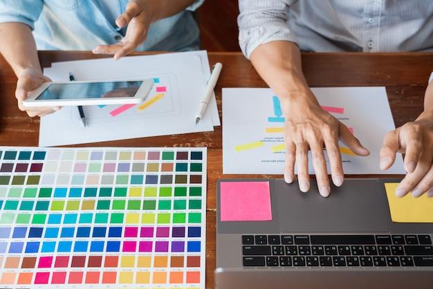 Designer de equipe criativa escolhendo amostras com ui / ux em desenvolvimento no layout do esboço