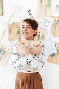 Designer de fahion adorável jovem segurando seu caderno