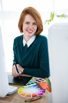 Designer de hipster sorridente, sentado em sua mesa, em um tablet digital