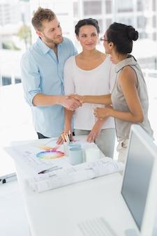 Designer de interiores apertando as mãos com o cliente feliz