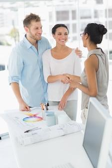 Designer de interiores apertando as mãos com o cliente sorridente