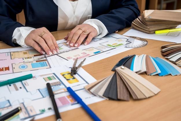 Designer de interiores com amostra de cores e planos de construção no escritório