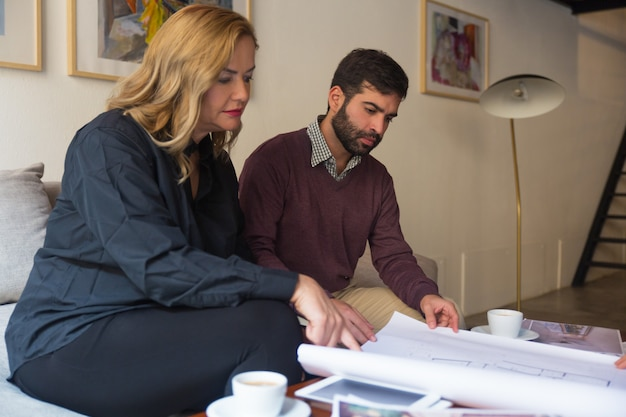 Designer de interiores e cliente estudando blueprint