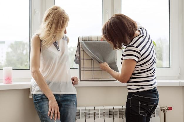 Designer de interiores mostra amostras de tecidos e acessórios para cortinas na casa nova