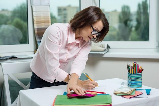 Designer de interiores, no local de trabalho no escritório com amostras de tecidos
