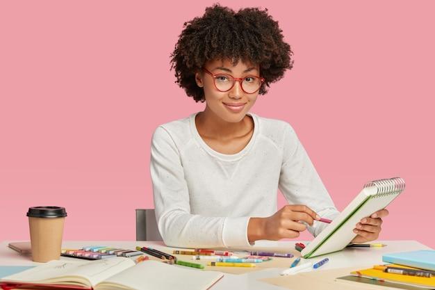 Designer de interiores ou artista gráfico de pele escura faz desenhos em cadernos, tem inspiração para trabalhar