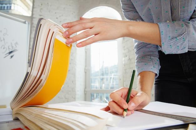 Designer de interiores profissional ou arquiteto trabalhando com paleta de cores, desenhos de quartos em escritórios modernos. jovem modelo feminino planejando futuro apartamento ou casa, escolhendo cores e derocation.