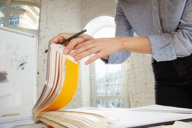 Designer de interiores profissional ou arquiteto trabalhando com paleta de cores, desenhos de salas em escritórios modernos