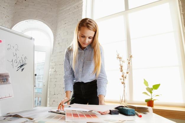 Designer de interiores profissional trabalhando com desenhos de salas em um escritório moderno