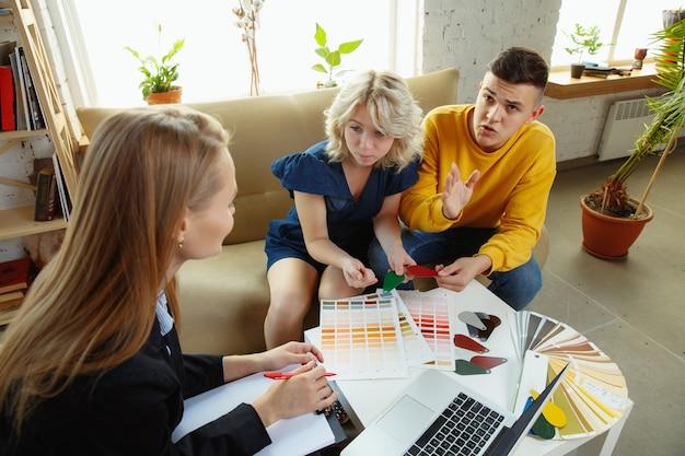 Designer de interiores trabalhando com jovem casal. família adorável e designer ou arquiteto profissional discutindo o conceito do futuro interior, trabalhando com paleta de cores, desenhos de quartos em um escritório moderno.