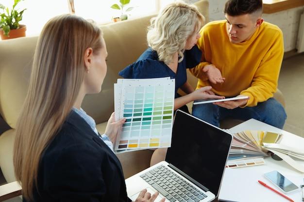 Designer de interiores trabalhando com jovem casal.