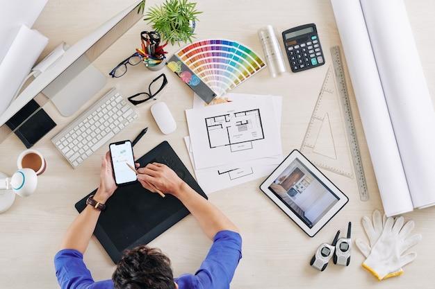 Designer de interiores verificando smartphone