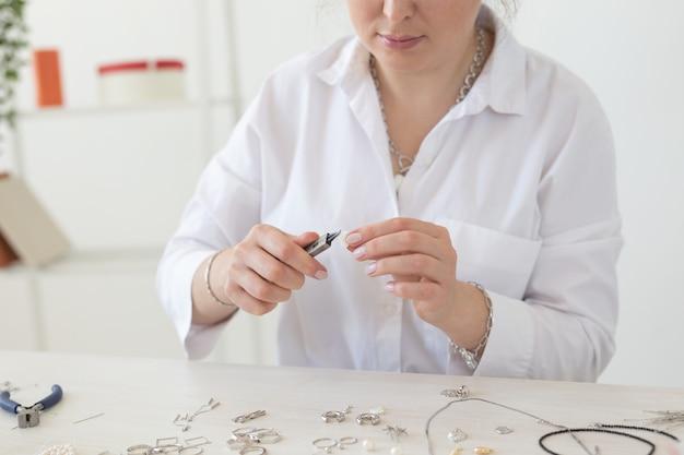Designer de joias profissional fazendo joias feitas à mão em close-up de oficina de estúdio. moda, criatividade e conceito artesanal