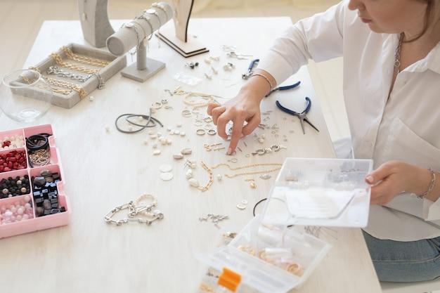 Designer de joias profissional fazendo joias feitas à mão em estúdio oficina closeup moda criatividade