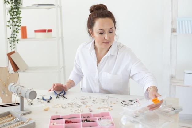 Designer de joias profissional fazendo joias feitas à mão na oficina. moda, criatividade e conceito artesanal.