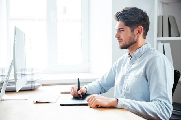 Designer de jovem bonito e focado trabalhando usando computador e tablet gráfico no escritório