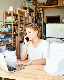 Designer de jovem empreendedor feminino falando no celular e olhando para o laptop e sorridente, feliz senhora em um dia ensolarado na oficina. pequena empresa feminina