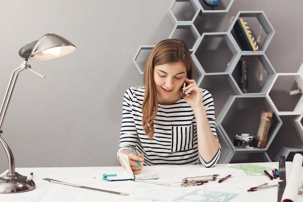 Designer de jovem empresário bonito com cabelos escuros na camisa listrada, falando no telefone com o cliente discutindo detalhes do design do site e escrevendo-os no caderno antes de se encontrar na vida real