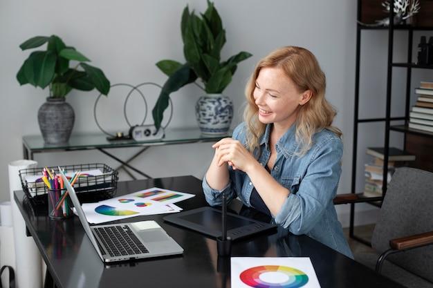 Designer de logotipo feminino trabalhando em seu escritório em um tablet gráfico