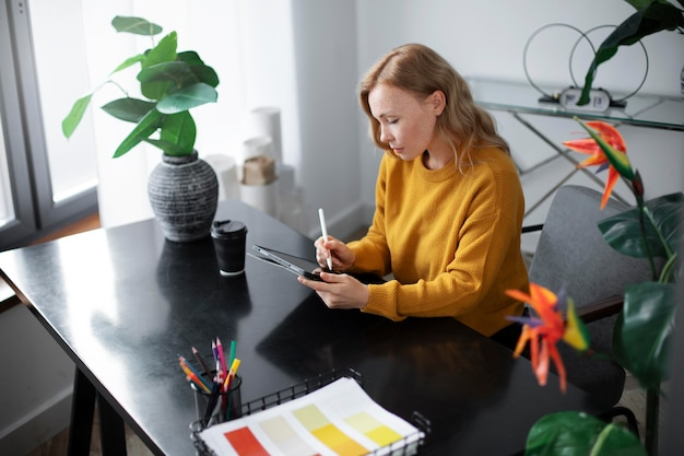 Designer de logotipo feminino trabalhando em um tablet gráfico