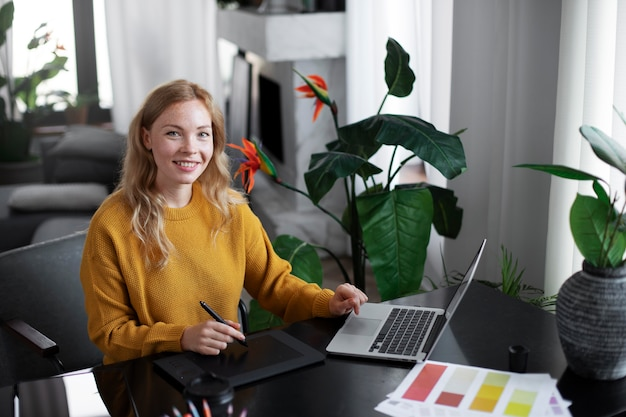 Designer de logotipo trabalhando em seu tablet conectado a um laptop