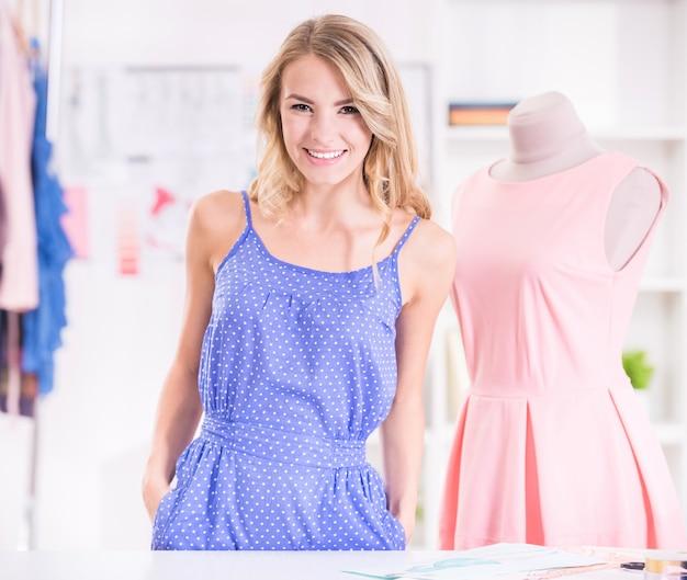 Designer de loira feminino em pé perto de manequim.