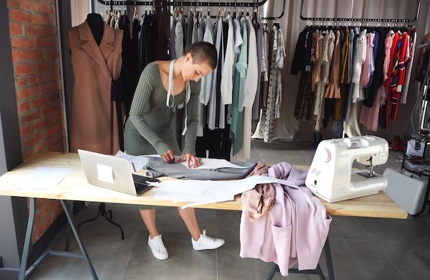 Designer de moda atraente com cabelo curto, trabalhando em ateliê, atelier