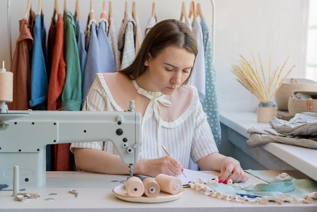 Designer de moda desenhando roupas e esboçando enquanto está sentada no local de trabalho com a máquina de costura