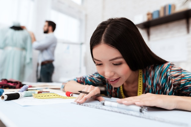 Designer de moda desenho com régua om papel.