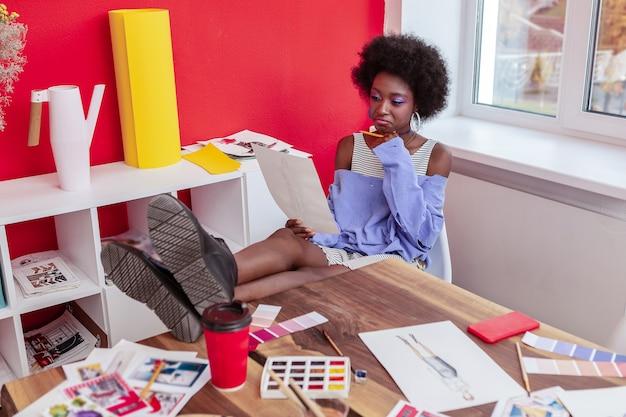 Designer de moda. designer de moda atraente e elegante sentado à mesa enquanto trabalha na nova coleção