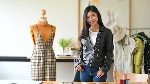Designer de moda em pé perto de manequim em estúdio.
