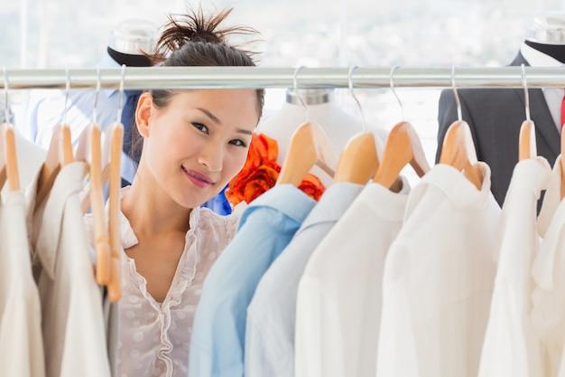Designer de moda feminina bonita com rack de roupas