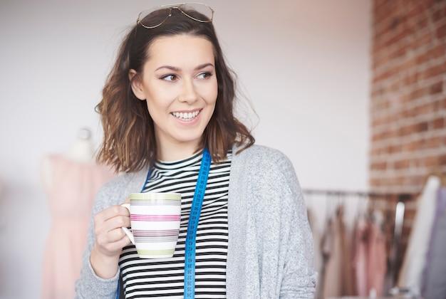 Designer de moda feminina com uma xícara de café