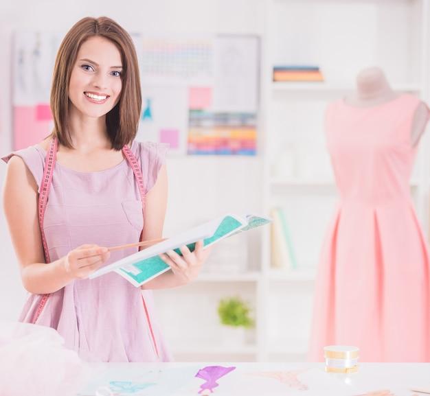 Designer de moda feminina olhando para a câmera e sorrindo.