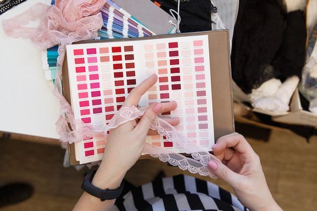 Designer de moda feminina segurando amostras de cores escolhendo tecido têxtil no local de trabalho, costureira ou alfaiate trabalhando na mesa, apontando para a paleta definida, fazendo a seleção de opções, vista de perto