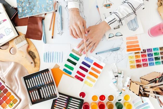Designer de moda feminina, trabalhando em esboços com tinta