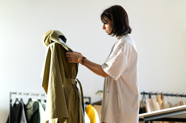 Designer de moda feminina trabalhando no ateliê ajeitando roupas no manequim para apresentação da nova coleção