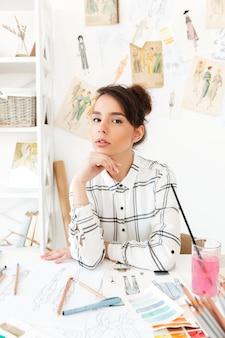 Designer de moda jovem bonita sentada em sua mesa de trabalho