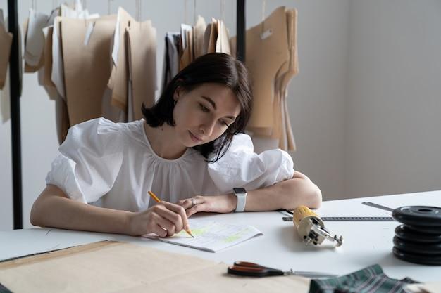 Designer de moda jovem escreve notas de medidas planejando uma nova coleção no estúdio de costura