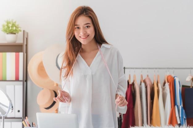 Designer de moda linda mulher asiática em pé na loja de roupas