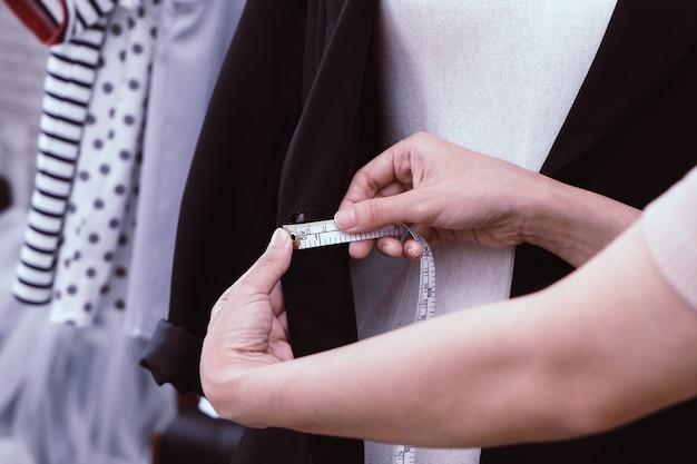 Designer de moda mão está medindo roupas com fita métrica