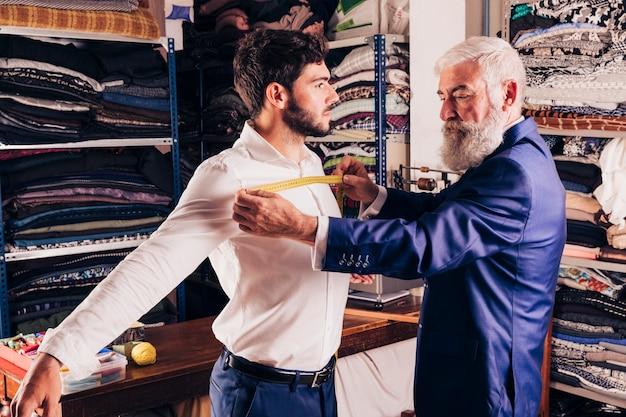 Designer de moda masculina profissional, tendo a medição do peito do seu cliente