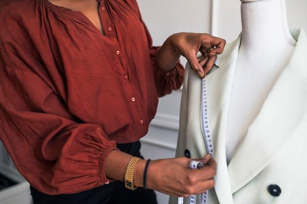 Designer de moda medindo um blazer em um manequim pinnable