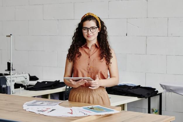 Designer de moda muito criativo usando tablet enquanto percorre recursos de novas tendências e escolhe esboços de roupas